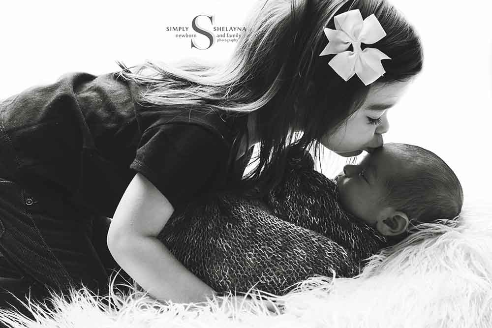 Lia kissing Joey sibling pose  CNY Newborn Photography